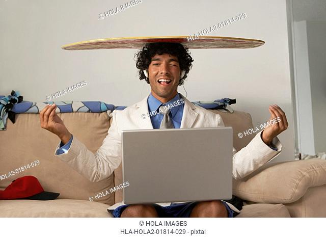 Young man sitting with a laptop in his lap and a body board on his head