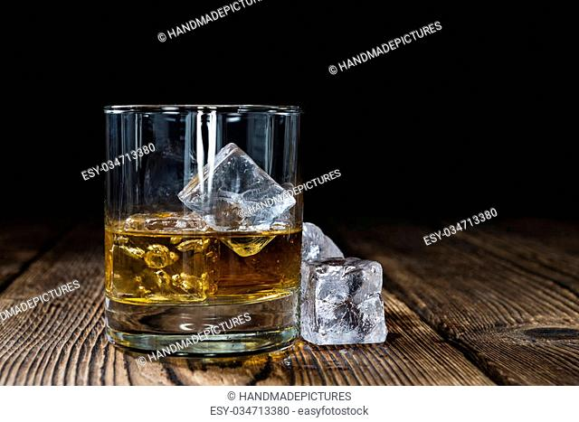 Glass with Whiskey and Ice on wooden background