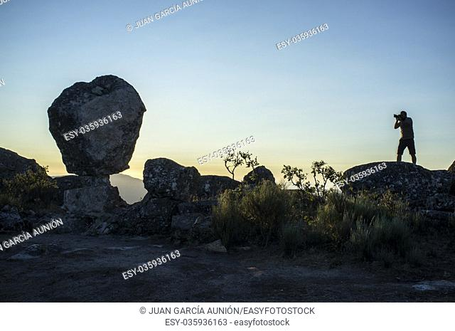 Silhouette of a photographer shooting sun rising above the mountain. Montanchez Famous megalithic monument, Caceres, Spain