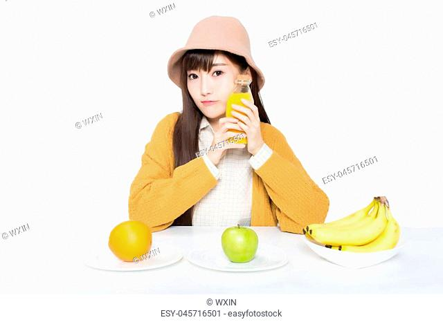 girl sitting in a classroom, apples and oranges arrayed on the desk as well as milk