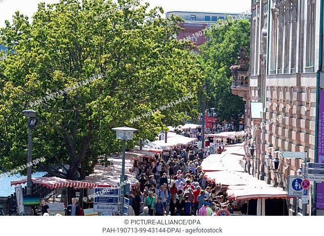 13 July 2019, Berlin: Passers-by stroll in sunny weather over the antique market next to the German Historical Museum (DHM). Photo: Soeren Stache/dpa
