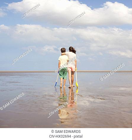 Brother and sister with shovels hugging and looking at sunny ocean