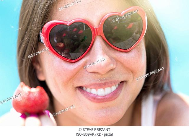 Close up portrait of young woman eating strawberry