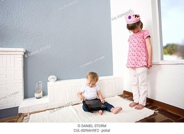 Girl watching over baby boy playing digital tablet