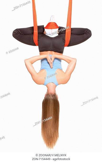 Young woman doing anti-gravity aerial yoga in hammock on a seamless white background