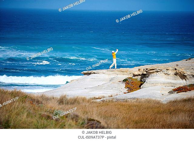 High angle view of golfer standing on cliff overlooking ocean taking golf swing