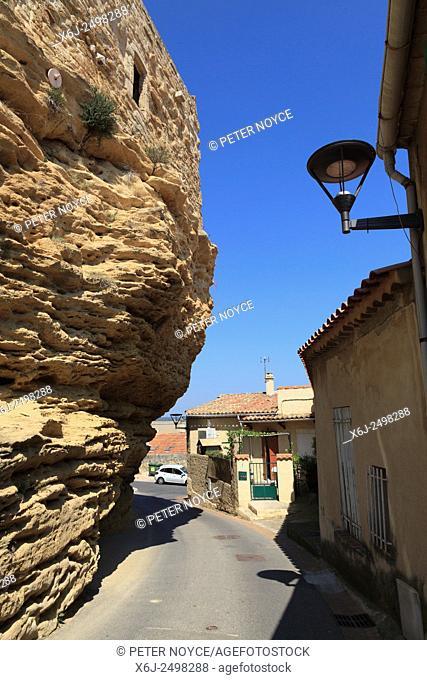 Village road running beneath overhanging rock