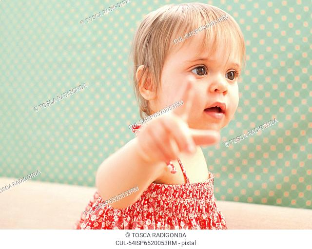 Baby girl pointing outdoors