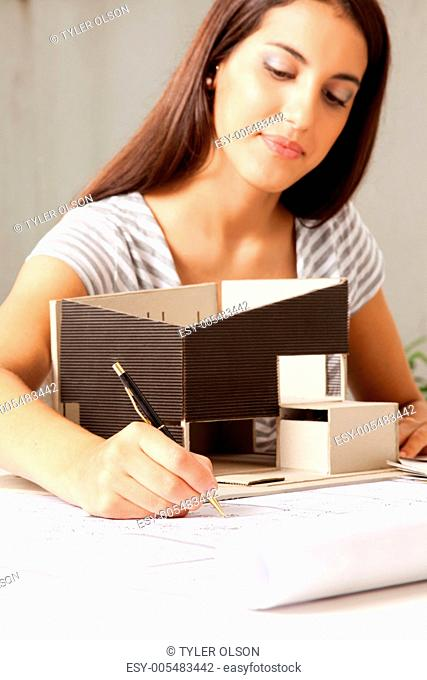 Young Female Architect with Model house