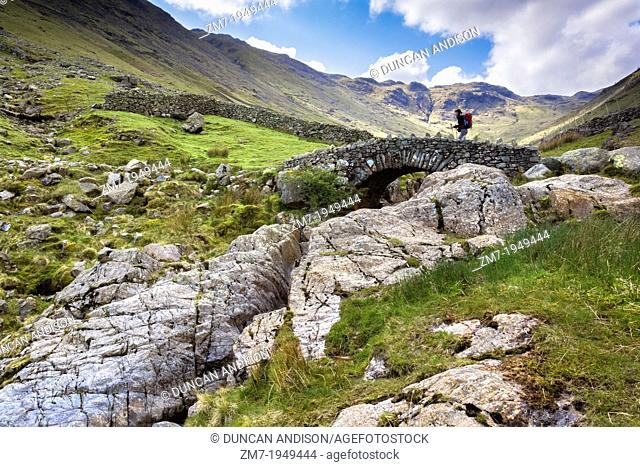 A hiker crosses Stockley Bridge on a bright spring day from Seathwaite Fell in the Lake District, Cumbria UK