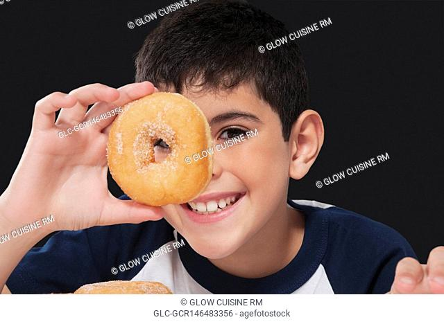 Boy holding a donut in front of his eye