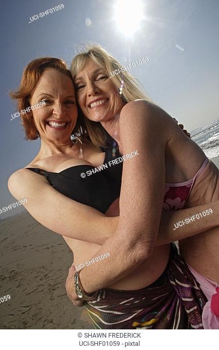 Mature women hugging at the beach