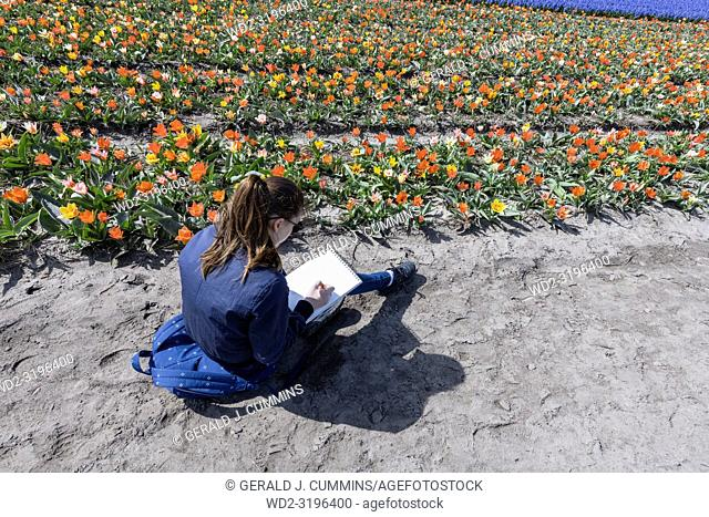 A Girl enjoying a field of flowers in Holland,