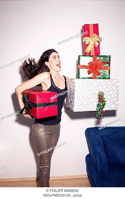 Young woman balancing large gift boxes