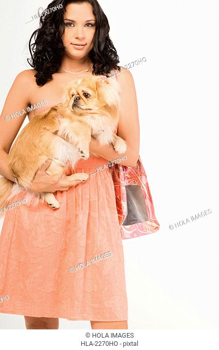 Portrait of a young woman carrying a Pomeranian dog