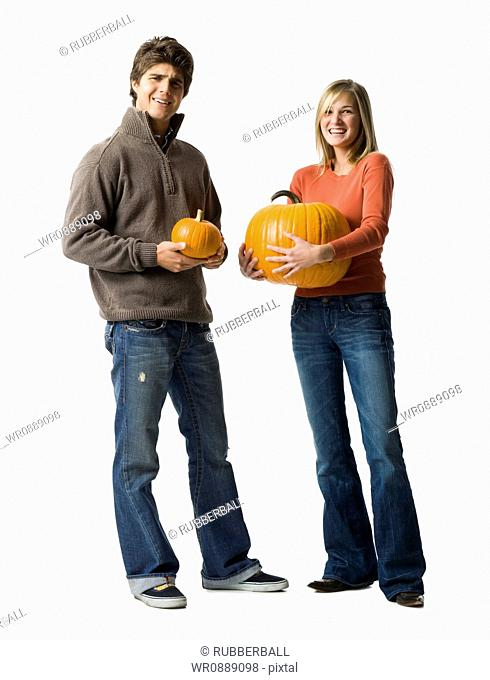 Portrait of a young couple holding pumpkins