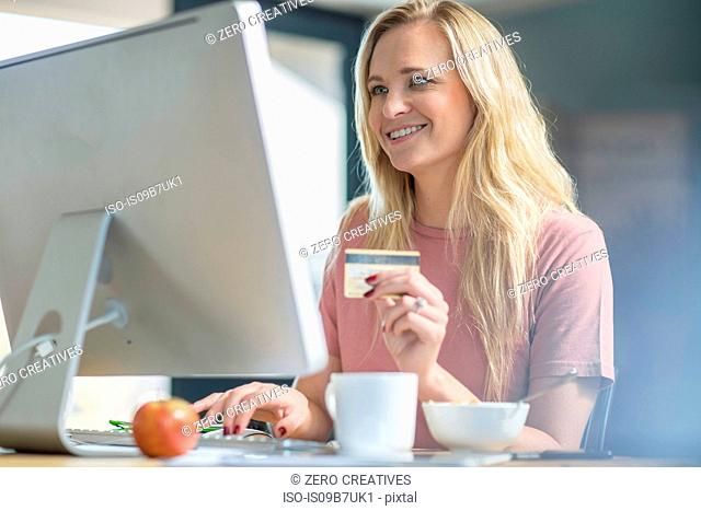 Woman holding credit card using computer smiling