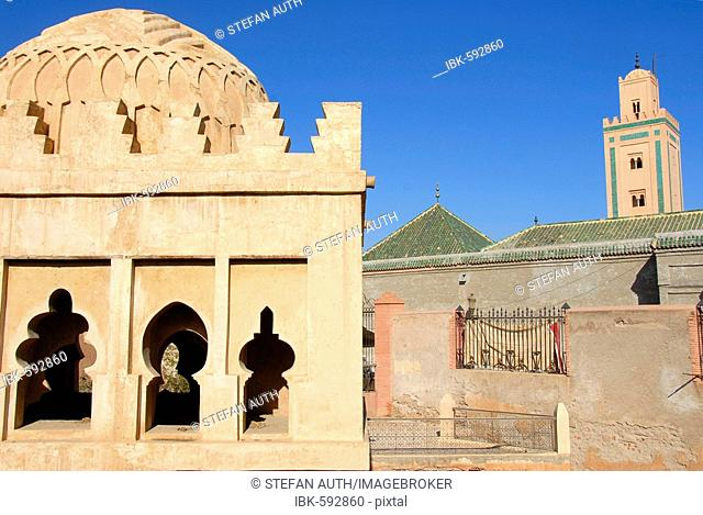 Ancient Berber decorated cupola building Koubba Ba'adyin with minaret of mosque Ali Ben Youssouf medina Marrakech Morocco
