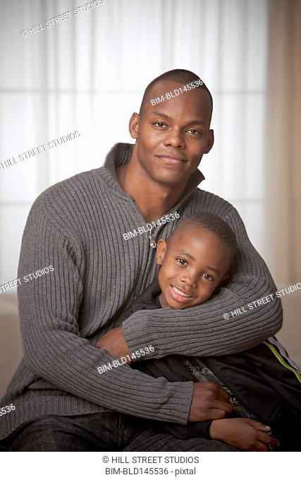 Black father hugging son