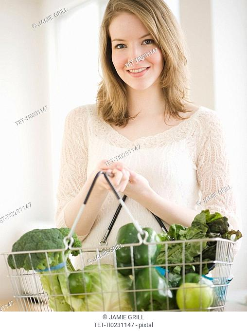 Woman holding basket of green vegetables