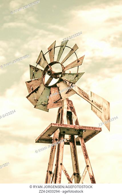 Weathered and vintage Aermotor windmill utilising wind energy to pump water for cattle on an outback Australian farm. Agricultural architecture