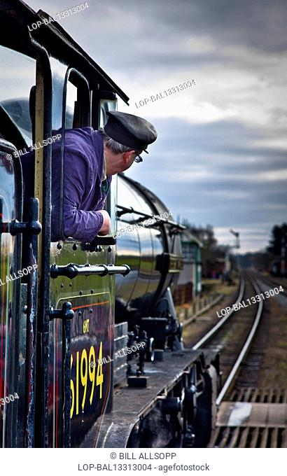 England, Leicestershire, Quorn. The engine driver looks out of the cab of a steam engine on the Great Central Railway at Quorn Station