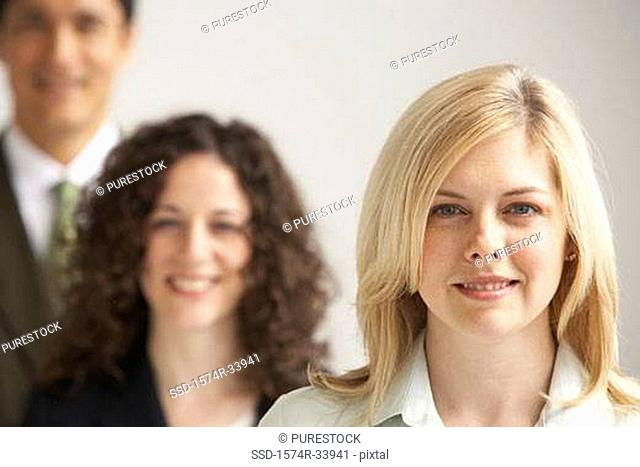 Portrait of two businesswomen and a businessman smiling