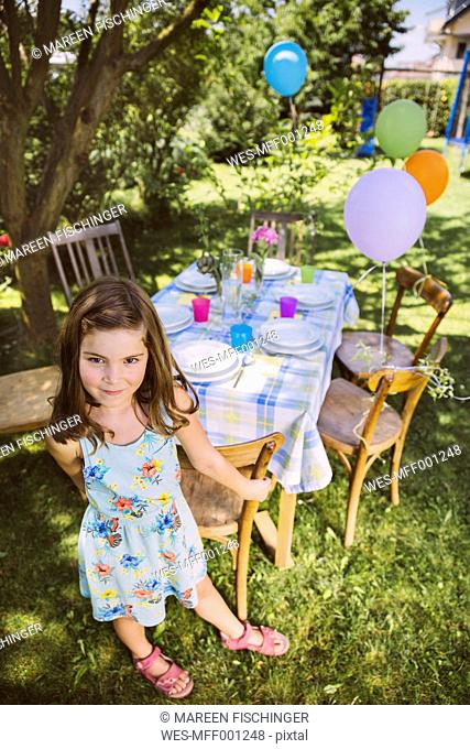 Girl with balloons in garden