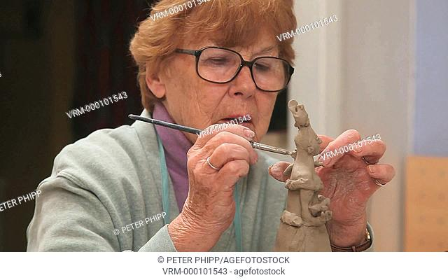 Senior woman artist working with a ceramic sculpture in a studio