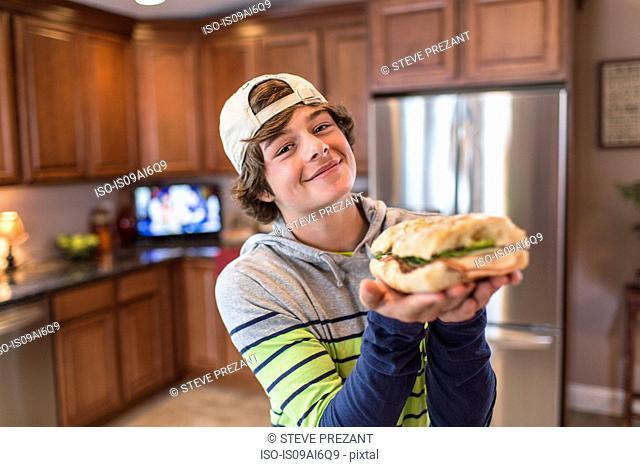 Teenage boy in kitchen holding sandwich