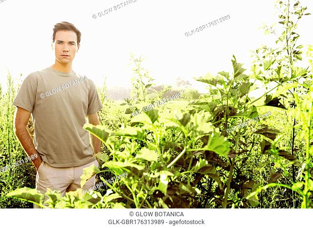 Man standing in a field with hands in his pockets