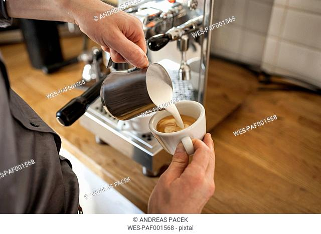 Cappuccino, man pouring milk froth in coffee cup
