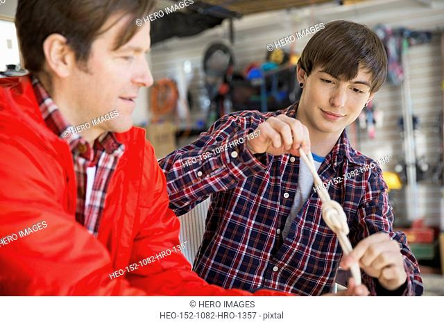 Father teaching son to tie knots in garage