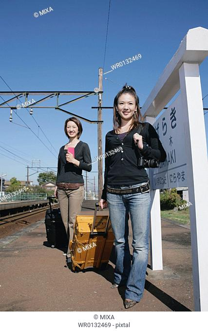 Two young women standing on train platform
