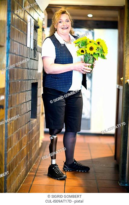 Portrait of mid adult woman with prosthetic leg, standing, holding flowers