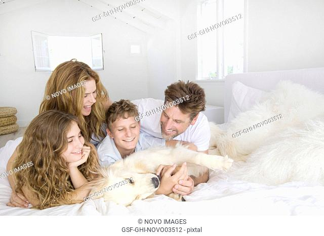 Happy Family Laying on Bed with Pet Dog