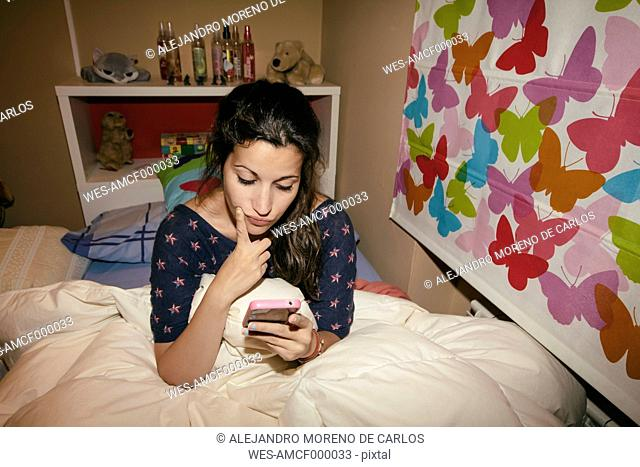 Spain, Madrid, young woman sitting on bed and using smart phone