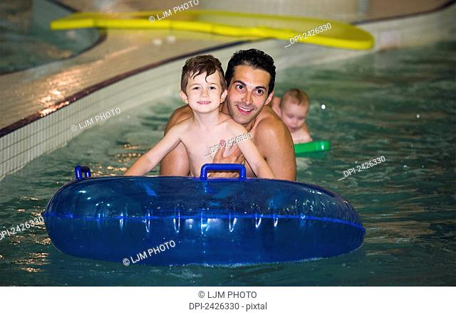 Father and son playing in a swimming pool on an inflatable tube; Edmonton, Alberta, Canada