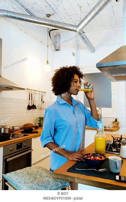 Woman having breakfast in her kitchen, drinking orange juice