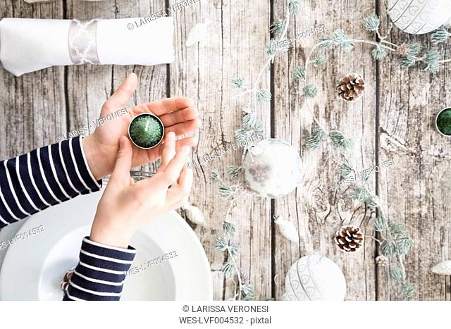 Girl's hands holding tea light in front of laid table at Christmas time