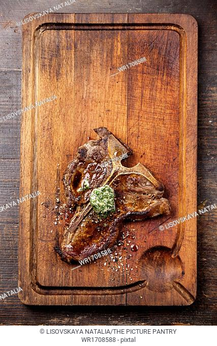 Grilled T-Bone Steak and herbs butter on meat cutting board