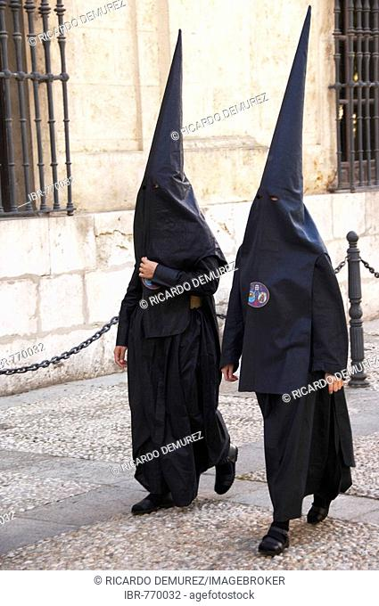 Penitants dressed in black penitential robes (nazareno) on their way to the Semana Santa, Holy Week procession, Seville, Andalusia, Spain