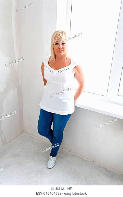 Blond woman in red and black jeans stand inside empty room near window