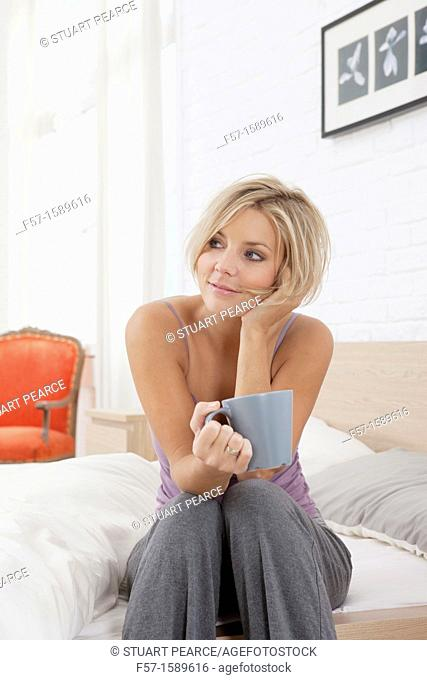 Young woman sitting on the edge of her bed drinking coffee