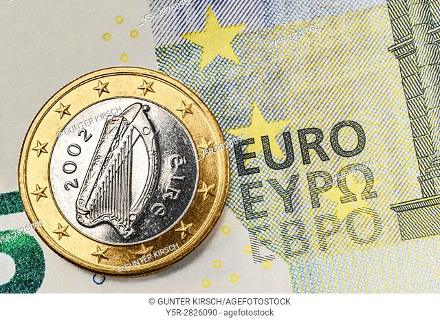 a 1 euro coin from Ireland on a 5 euro banknote