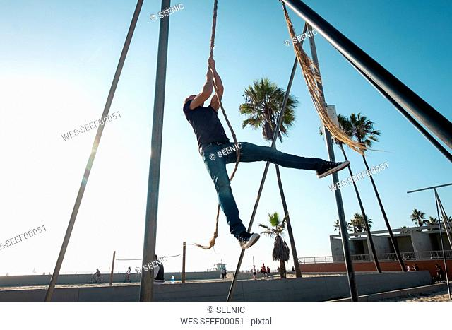USA, California, Los Angeles, Venice, Man on the rope at Muscle Beach