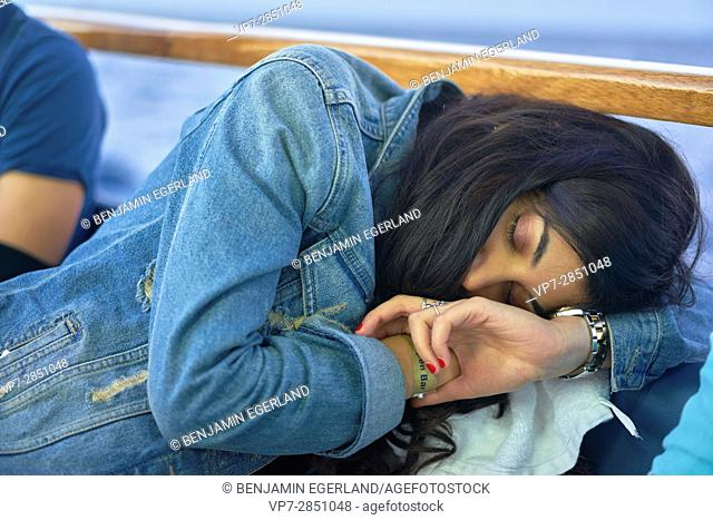 Young relaxed student woman sleeping in bar next to ocean