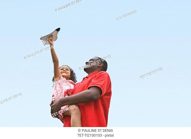 Child playing with toy plane