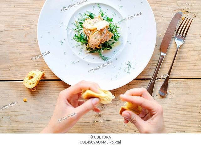 Female hands eating bread with roasted guinea fowl on greens with tarragon