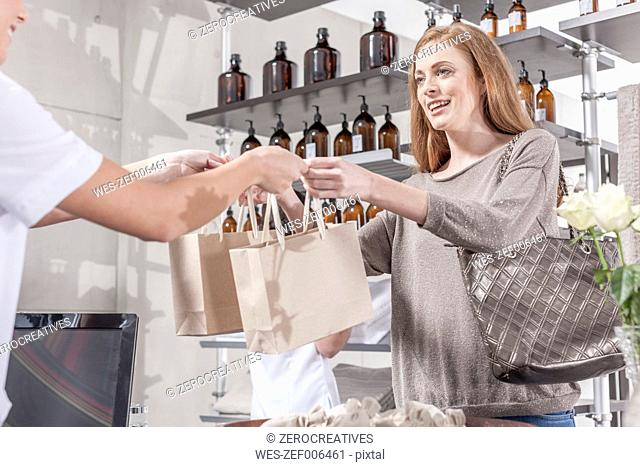Shop assistant in wellness shop handing over bags to client